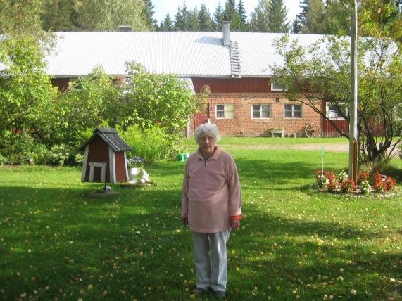 Bertta Seppänen kotitalonsa pihalla. Taustalla on 1949 valmistunut nTauno Joensuun ja oik. Mikko Kultasen siirtotilat 2014 ovat edelleen suvuilla. Navetat tehtiin myös tyyppipiirustuksilla.