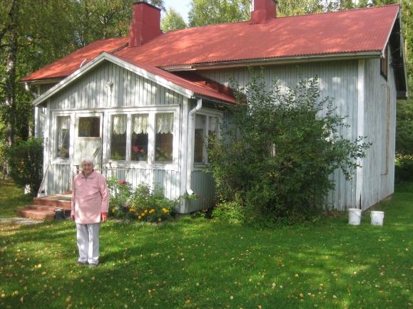 Bertta Seppänen talonsa pihalla. Vuonna 1941 olleet pienet koivut ovat nyt suuria varjostavia puita.